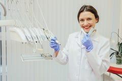 Conceito dos povos, medicina, odontologia e cuidados médicos - dentista feliz da jovem mulher com as ferramentas acima do fundo d fotografia de stock royalty free