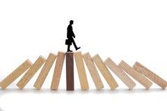 Conceito dos riscos comerciais, homem de negócios que anda em blocos de madeira imagens de stock