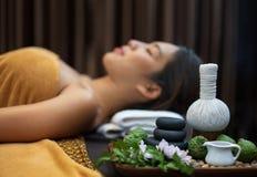 Conceito dos termas, pedras do zen, velas e flores no fundo da mulher que recebe o tratamento, mulher bonita nova nos termas imagens de stock