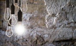 Conceito dos trabalhos de equipa e da inovação - bulbos no fundo da parede Foto de Stock Royalty Free