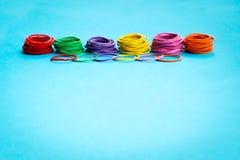 Conceito dos trabalhos de equipa grupo de elástico colorido no fundo azul com espaço da cópia Imagem de Stock Royalty Free