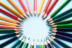 Conceito dos trabalhos de equipa grupo de lápis da cor no fundo azul fotos de stock royalty free