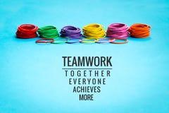 Conceito dos trabalhos de equipa o grupo de elástico colorido no fundo azul com trabalhos de equipa da palavra, junto, todos, con Imagens de Stock