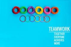 Conceito dos trabalhos de equipa o grupo de elástico colorido no fundo azul com trabalhos de equipa da palavra, junto, todos, con Foto de Stock Royalty Free