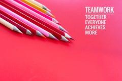Conceito dos trabalhos de equipa o grupo de lápis da cor no fundo cor-de-rosa com trabalhos de equipe da palavra, junto, todos, c imagem de stock royalty free