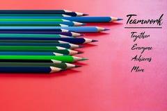 Conceito dos trabalhos de equipa o grupo de lápis da cor no fundo vermelho com trabalhos de equipe da palavra, junto, todos, cons imagem de stock