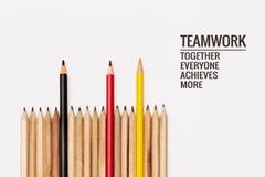 Conceito dos trabalhos de equipa o grupo de lápis no fundo branco com trabalhos de equipe da palavra, junto, todos, consegue e ma imagem de stock