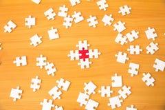 Conceito dos trabalhos de equipa usando as partes brancas e vermelhas do enigma que estão sendo cabidas imagem de stock