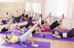 Conceito e ideias da aptidão Grupo de um esticão de sete pés de Performng dos atletas fêmeas Imagens de Stock