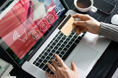 Conceito em linha de compra Mulher que mantém o cartão de crédito do ouro compra disponivel e em linha usando-se no portátil em c Imagem de Stock