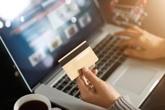 Conceito em linha de compra Mulher que mantém o cartão de crédito do ouro compra disponivel e em linha usando-se no portátil em c Imagens de Stock Royalty Free