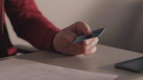Conceito em linha dos pagamentos estoque O homem de negócio guarda um cartão de crédito em sua mão ao usar ou ao datilografar a i foto de stock