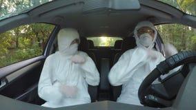 Conceito engraçado de dois trabalhadores novos dos cientistas do hazmat na dança e na condução do carro ao lugar contaminado - vídeos de arquivo