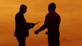 Conceito ereto da prancheta da luz solar da silhueta do por do sol da discussão do homem de negócios dois homens do homem de negó vídeos de arquivo
