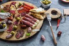 Conceito espanhol típico dos tapas inclua o jamon das fatias da variedade, chouriço, salame, bacias com azeitonas, pimentas Copys imagem de stock
