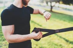 Conceito esperto saudável do estilo de vida Atleta muscular que faz grande TRX de exercício fora no parque ensolarado Homem consi foto de stock
