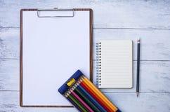 Conceito estacionário, caderno vazio e papel vazio na prancheta de madeira Imagem de Stock Royalty Free