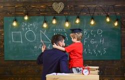 Conceito favorito do professor O professor com barba, pai ensina o filho pequeno na sala de aula, quadro no fundo Menino fotos de stock