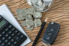 Conceito financeiro como a chave do carro com a pilha de moeda, vaia da nota do lápis Foto de Stock