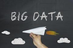 Conceito grande dos dados tirado no quadro-negro com a mão que guarda o avião de papel foto de stock