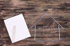 Conceito Home A casa modelo de madeira em uma tabela de trabalho com ferramentas e esvazia o caderno espiral Imagem de Stock Royalty Free