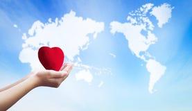 Conceito humano internacional do dia da solidariedade: mãos que guardam o seguro de saúde vermelho do coração fotografia de stock