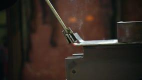 Conceito industrial Povos que trabalham em uma planta Um homem que dobra-se acima do detalhe caloroso do metal filme