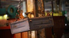 Conceito industrial Um guindaste de levantamento industrial com uma corrente em guardar uma caixa do metal video estoque