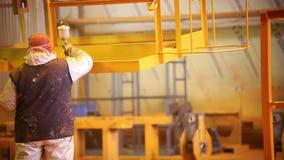 Conceito industrial Um trabalhador do homem nas luvas que guardam um dispositivo de pulverização filme