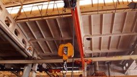 Conceito industrial Uma planta da construção Um gancho de levantamento do ferro suspendido acima do teto video estoque