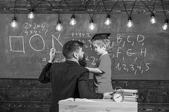 Conceito instrutivo da conversação O professor com barba, pai ensina o filho pequeno na sala de aula, quadro no fundo fotos de stock