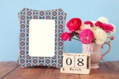 Conceito internacional do dia das mulheres com as flores bonitas no vaso e na data na tabela de madeira Imagens de Stock Royalty Free