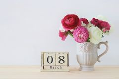Conceito internacional do dia das mulheres com as flores bonitas no vaso e na data na tabela de madeira Fotos de Stock Royalty Free