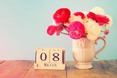 Conceito internacional do dia das mulheres com as flores bonitas no vaso e na data na tabela de madeira Fotografia de Stock Royalty Free