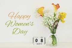 Conceito internacional do dia das mulheres com as flores bonitas no vaso e na data na tabela de madeira Fotos de Stock