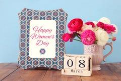 Conceito internacional do dia das mulheres com as flores bonitas no vaso e na data na tabela de madeira Foto de Stock