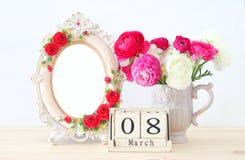 Conceito internacional do dia das mulheres com as flores bonitas no vaso e na data na tabela de madeira Imagem de Stock Royalty Free