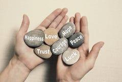Conceito interno do equilíbrio: mãos que guardam pedras com o happi das palavras Fotos de Stock Royalty Free