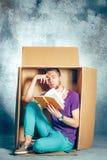 Conceito introvertido Homem que senta-se dentro da caixa e do livro de leitura fotos de stock