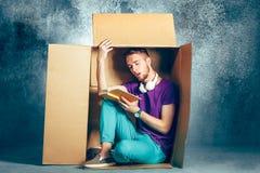 Conceito introvertido Homem que senta-se dentro da caixa e do livro de leitura imagens de stock royalty free