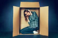 Conceito introvertido Mulher que senta-se dentro da caixa e que trabalha com portátil imagens de stock