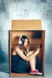Conceito introvertido Mulher que senta-se dentro da caixa e que trabalha com telefone imagem de stock