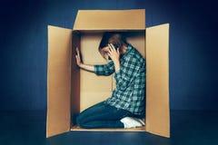Conceito introvertido Mulher que senta-se dentro da caixa e que trabalha com telefone fotos de stock royalty free