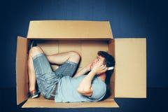 Conceito introvertido O homem que senta-se dentro da caixa e que trabalha com portátil imagens de stock