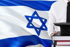 Conceito israelita bem sucedido da educação do estudante Guardando livros e tampão da graduação sobre o fundo da bandeira de Isra fotografia de stock royalty free