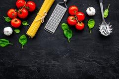 Conceito italiano da massa Os espaguetes, tomates, alho, ralador do queijo, colher para os espaguetes na opinião superior do fund imagens de stock royalty free