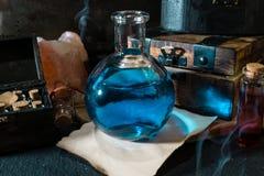 Conceito mágico Poção azul na garrafa e na caixa de madeira imagem de stock
