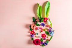 Conceito mínimo da Páscoa Forma do ovo com as orelhas do coelho feitas das flores fotografia de stock