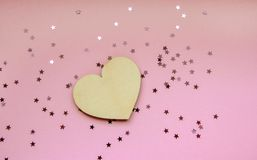 Conceito mínimo do coração de madeira contra o fundo cor-de-rosa pastel com confetes efervescentes das estrelas fotografia de stock