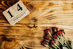 Conceito mínimo do dia de Valentim do St no fundo de madeira Rosas vermelhas e caledar de madeira com o 14 de fevereiro nele Imagens de Stock Royalty Free
